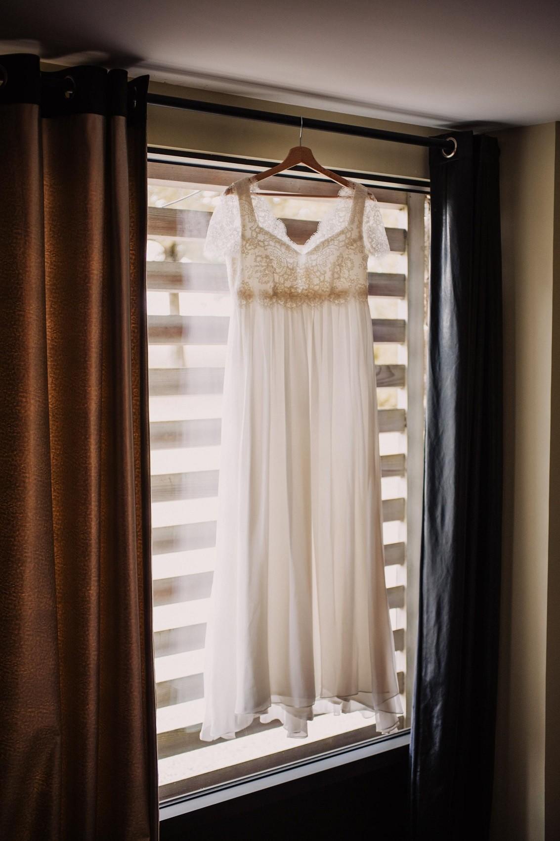 robe de mariée en dentelle de calais suspendu à la fenetre