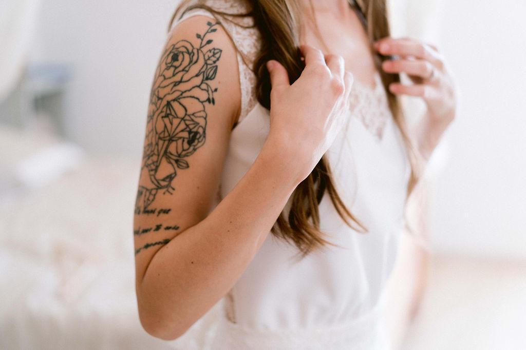 Les tatouages fleurie de la mariée sont parfait avec sa robe longue et simple.