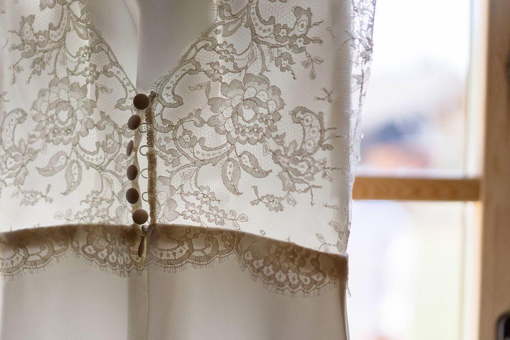 Une robe de mariée avec une joli dentelle de calais fermée par des boutons recouvert.