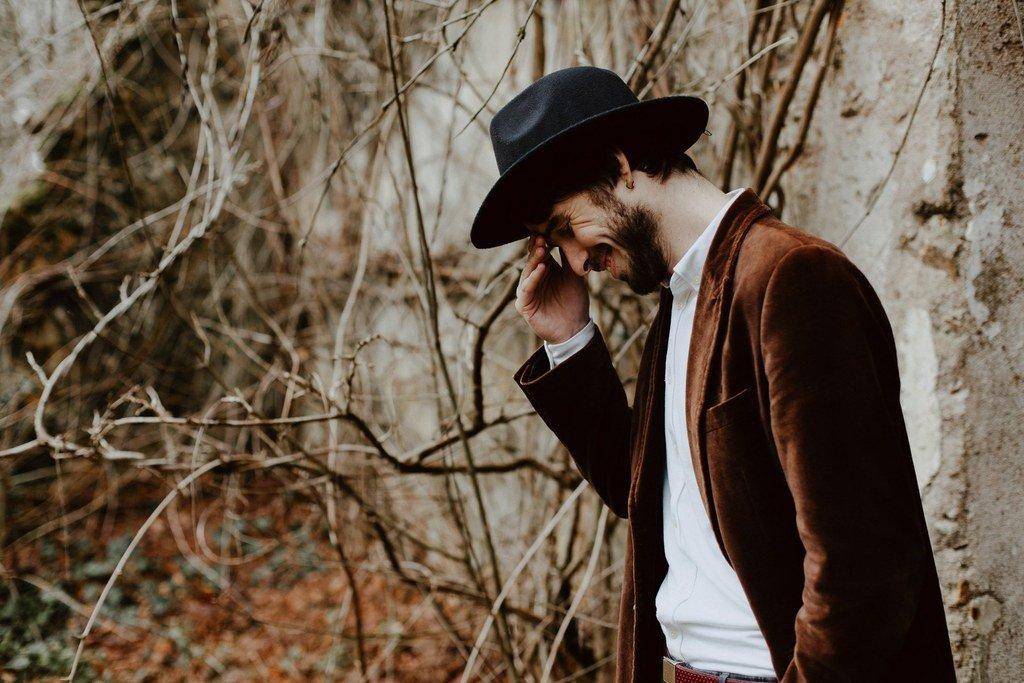 Le marié porte un chapeau noir et une belle veste en velours marron.