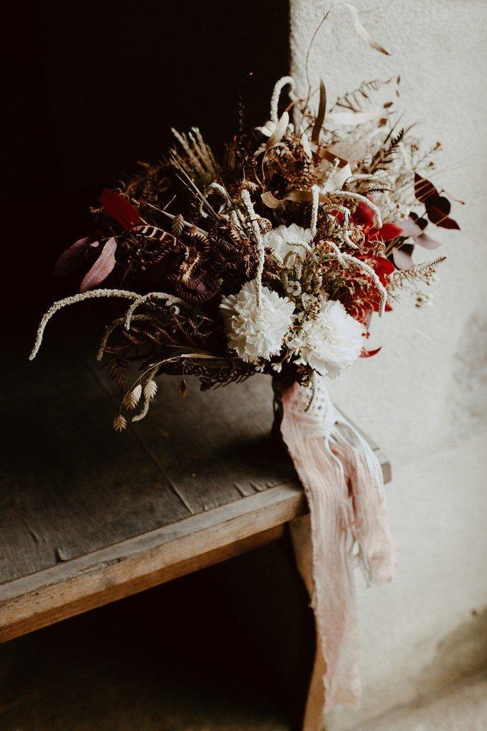 Ce bouquet composé de cymbidium, amarante, oeillet et was flower ainsi que pour le feuillage des fougères et de l'eucalyptus