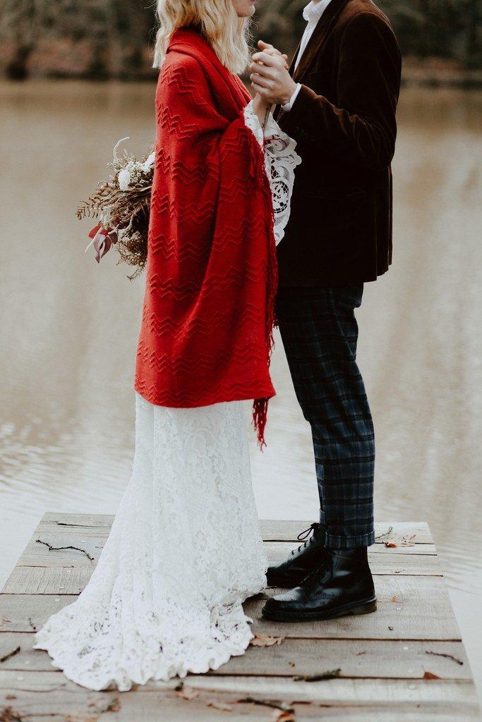 La mariée portait un plaide de mariée rouge en laine pour une effet original.