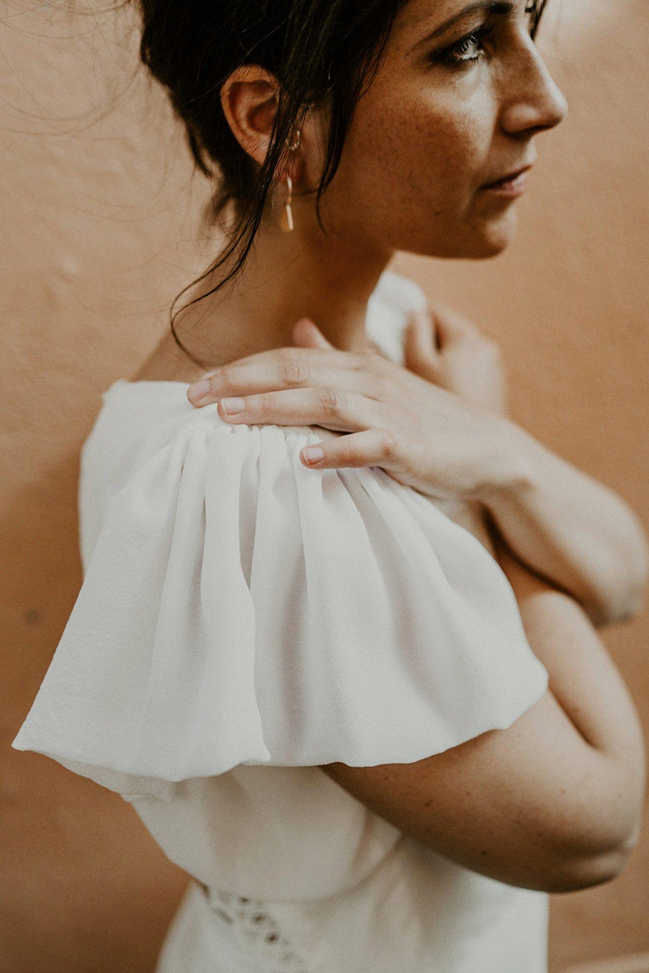 Cette robe de mariée très épure a des manches en mousseline de soie.